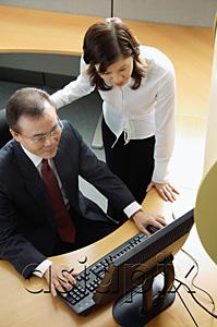 AsiaPix - Two business people looking at computer