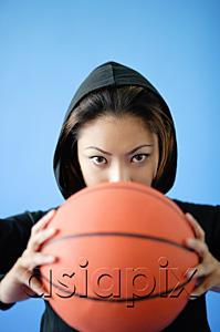 AsiaPix - Woman wearing hooded shirt, holding basketball over face