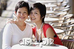 AsiaPix - Mother and adult daughter in cafe, smiling at camera