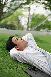 AsiaPix - Businessman lying on grass in park, looking up