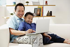 AsiaPix - Father and son in living room with laptop, smiling at camera