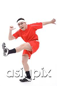 AsiaPix - Man in soccer uniform, kicking leg in air