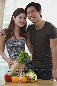 AsiaPix - Couple smiling at camera, fresh fruits and vegetables on table in front of them