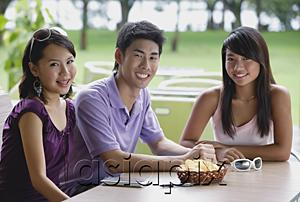 AsiaPix - Young adults sitting at outdoor cafe, smiling at camera