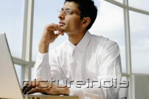 PictureIndia - Man using laptop, hand on chin, looking away