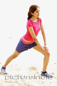 PictureIndia - Young woman at the beach, stretching