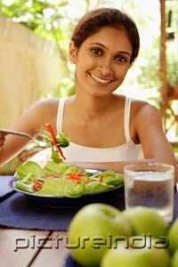 PictureIndia - Woman eating salad, looking at camera