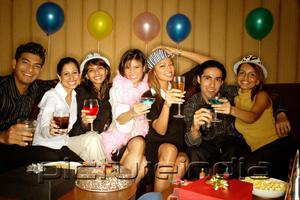 PictureIndia - Young adults sitting side by side, celebrating, holding drinks