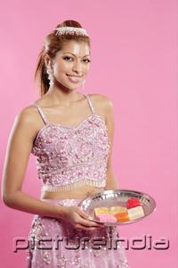 PictureIndia - Young woman in Indian costume, holding a tray of Indian sweets, smiling at camera
