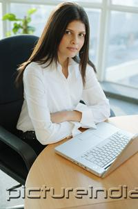 PictureIndia - Female executive sitting, arms crossed, laptop in front of her