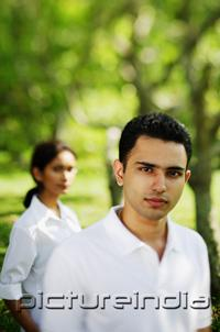 PictureIndia - Man looking at camera, woman in the background