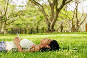 PictureIndia - Young woman lying on grass with headphones