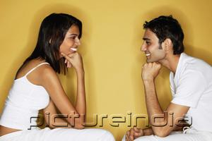 PictureIndia - Couple sitting face to face, hands on chin