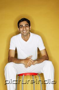 PictureIndia - Young man sitting on stool, looking at camera
