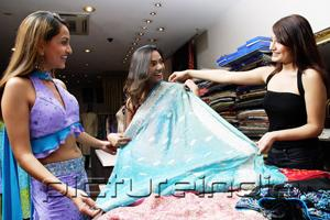 PictureIndia - Women in shop looking at cloth for saris