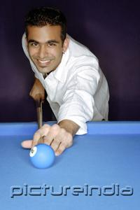 PictureIndia - Young man playing pool, smiling at camera, portrait