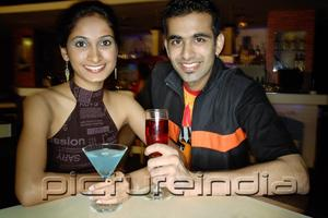 PictureIndia - Couple in a club with drinks, smiling at camera