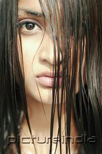 PictureIndia - Young woman looking at camera through long wet hair