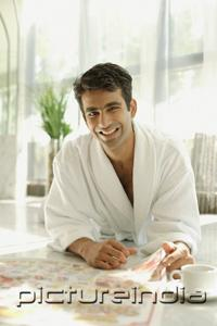 PictureIndia - Man in bathrobe, lying on floor, with newspaper, smiling at camera