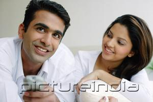 PictureIndia - Couple side by side, man holding TV remote control, woman looking at him
