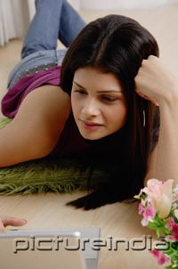 PictureIndia - Young woman using laptop, lying on floor, leaning on hand